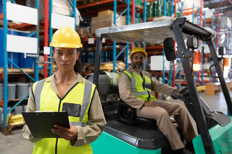 Female staff writing on clipboard in warehouse. Portrait of female staff writing on clipboard in warehouse. This is a freight transportation and distribution stock photography