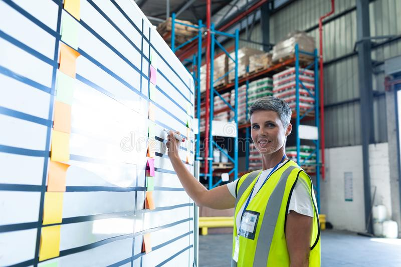 Female staff writing on whiteboard in warehouse. Portrait of beautiful Caucasian female staff writing on whiteboard in warehouse. This is a freight royalty free stock photography