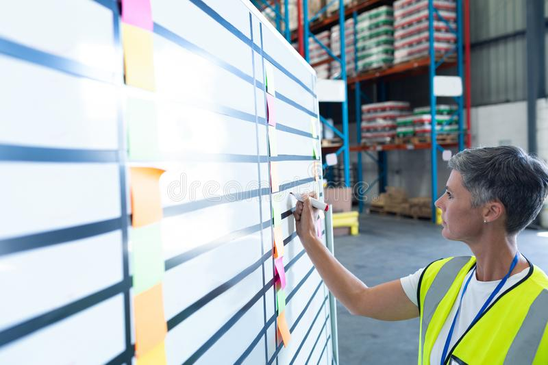 Female staff writing on whiteboard in warehouse. Side view of pretty mature Caucasian female staff writing on whiteboard in warehouse. This is a freight royalty free stock photo