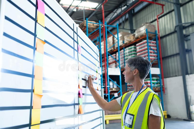 Female staff writing on whiteboard in warehouse. Side view of pretty mature Caucasian female staff writing on whiteboard in warehouse. This is a freight royalty free stock photography