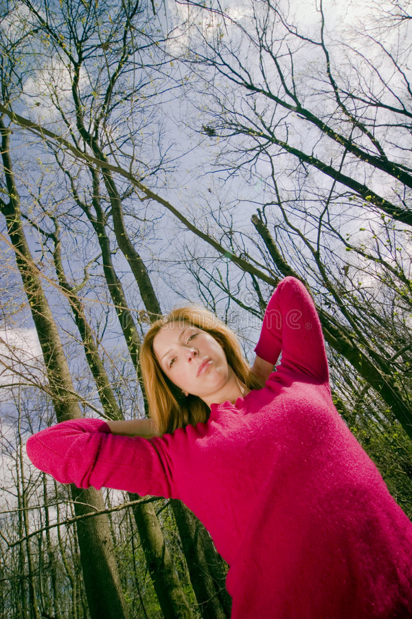 Female Standing in Forest. Young adult female stands in forest. Model wears a bright pink sweater and her elbows are raised in the air with her hands behind her stock photography