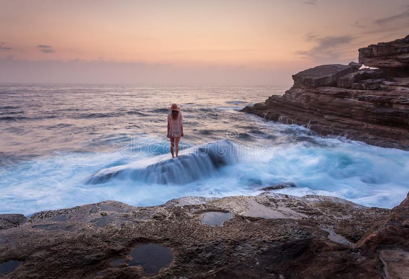 Female standing on shipwreck rock with ocean flowing over it royalty free stock photography