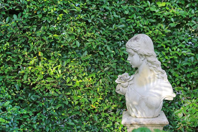 Female statue made from mortar in the summer garden with copy space. Decorative gardens.  royalty free stock photography