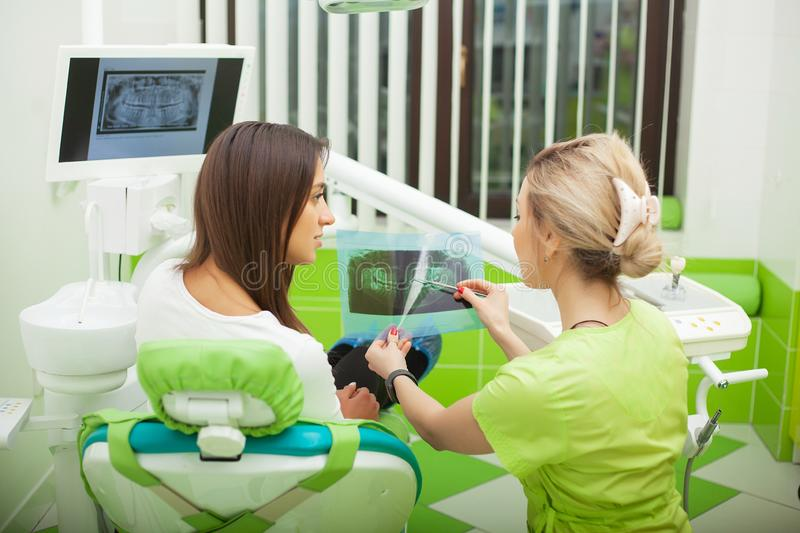 Female stomatologist in protective gloves examining patient`s teeth. Dentist caries treatment at dental clinic office.  royalty free stock photos