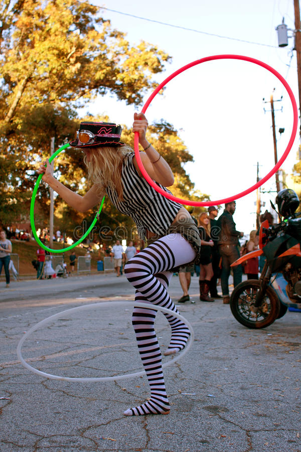 Female Street Performer Entertains With Three Hula Hoops stock photos