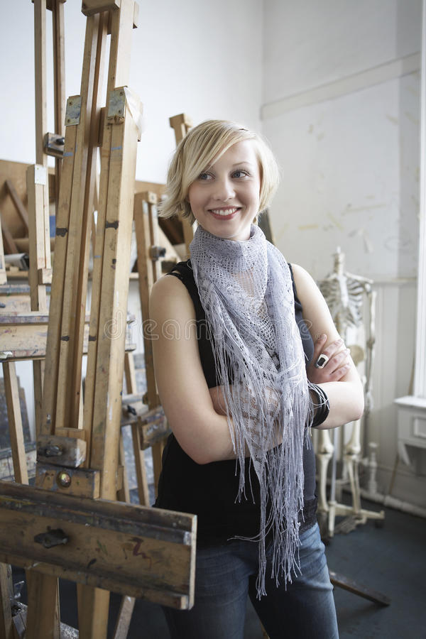 Female Student Amid Easels In Art College stock image