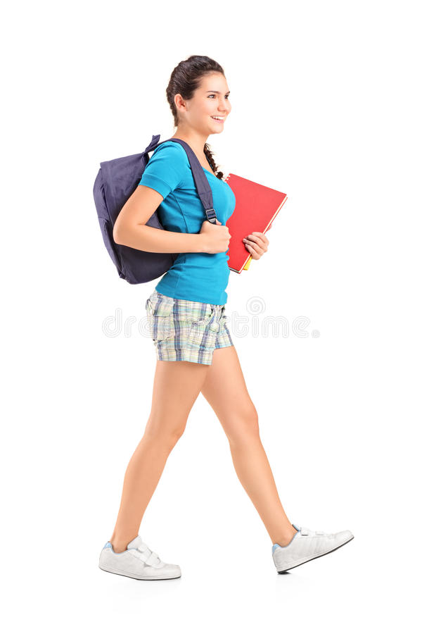 Female student with backpack walking and holding book