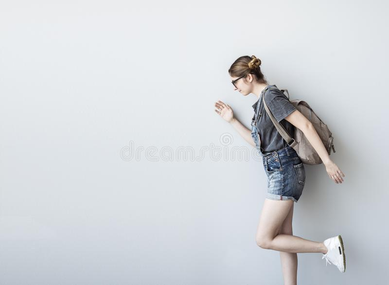 Female student with a backpack walking isolated on white background. Female student with a backpack walking isolated  on white background royalty free stock image