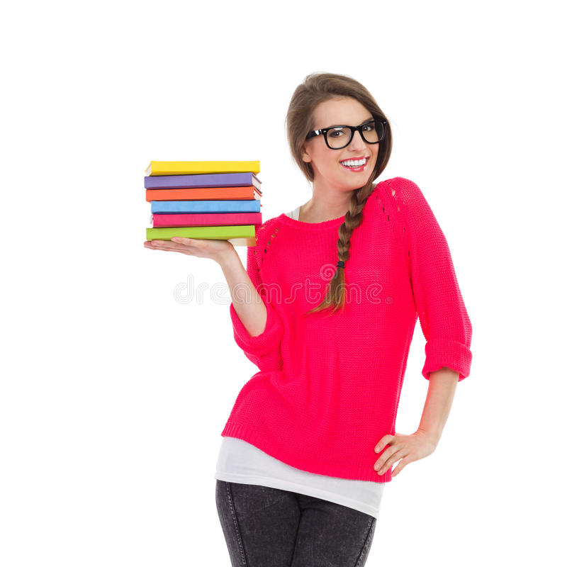 Female student with books. Smiling female student holding stack of book in one hand. Three quarter length studio shot isolated on white stock photography