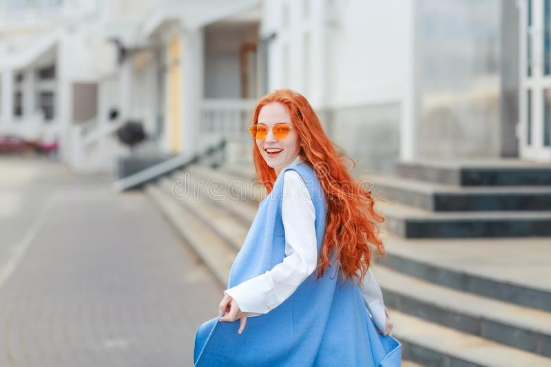A female student with bright long yellow hair walks around the city.  stock photos