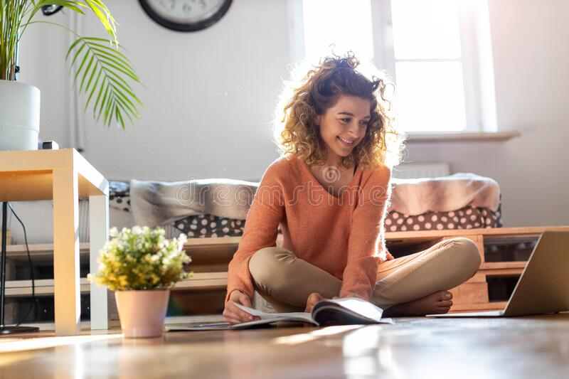Female student learning in home setting with laptop stock photo