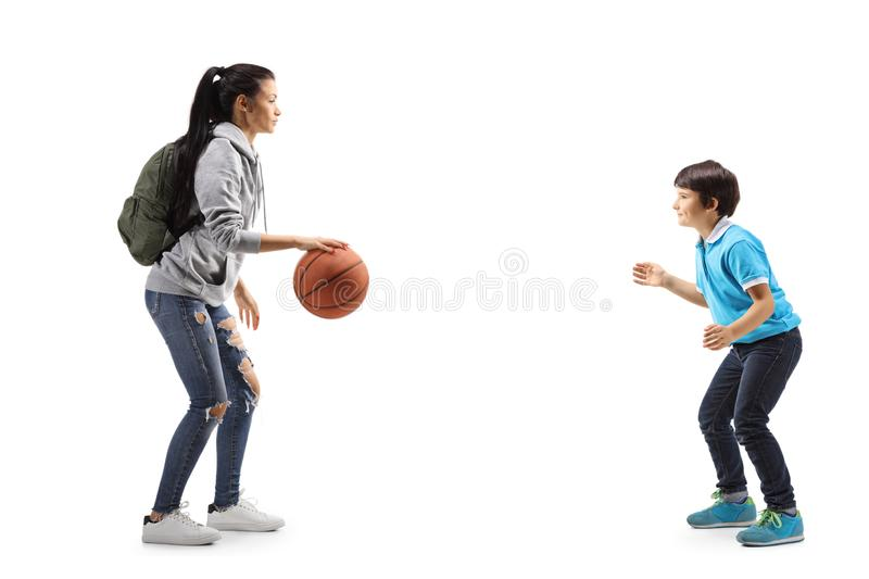 Female student and a little boy playing basketball royalty free stock images