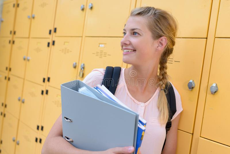 Female student next to lockers. Woman stock image