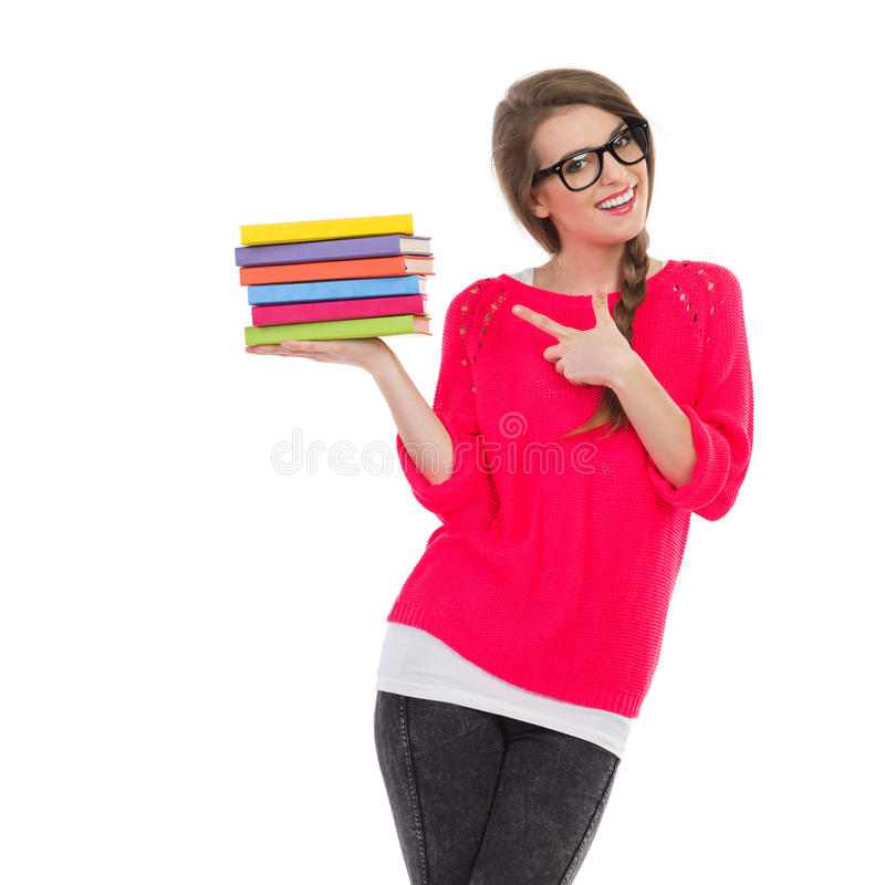 Female student pointing at a stack of books. Smiling female student holding a stack of book in one hand and pointing at them. Three quarter length studio shot royalty free stock images