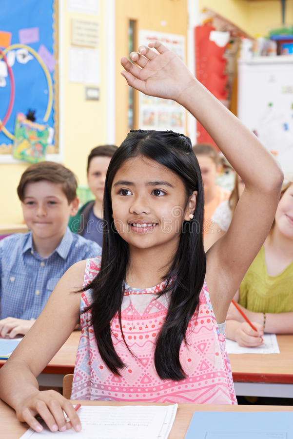 Female Student Raising Hand To Answer Question On Class stock image