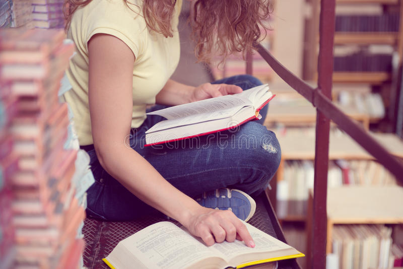 Female student reading book. S in library stock photography