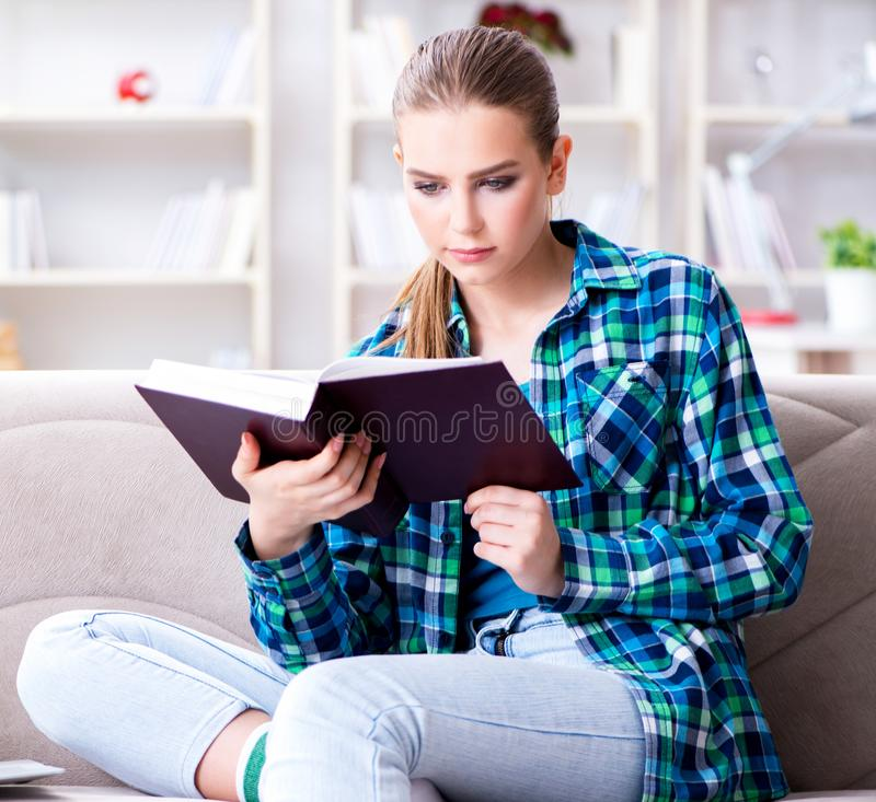 Female student reading the book  sitting on the sofa royalty free stock photos