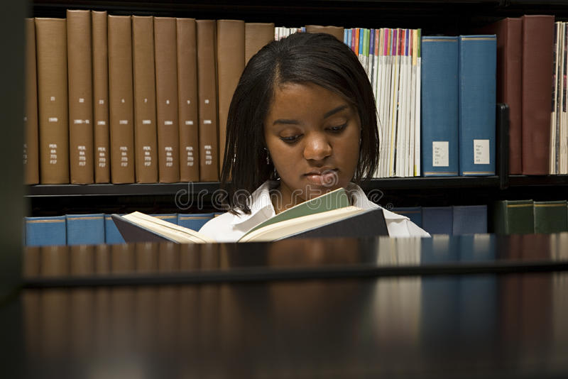 Female student reading in the library royalty free stock photos