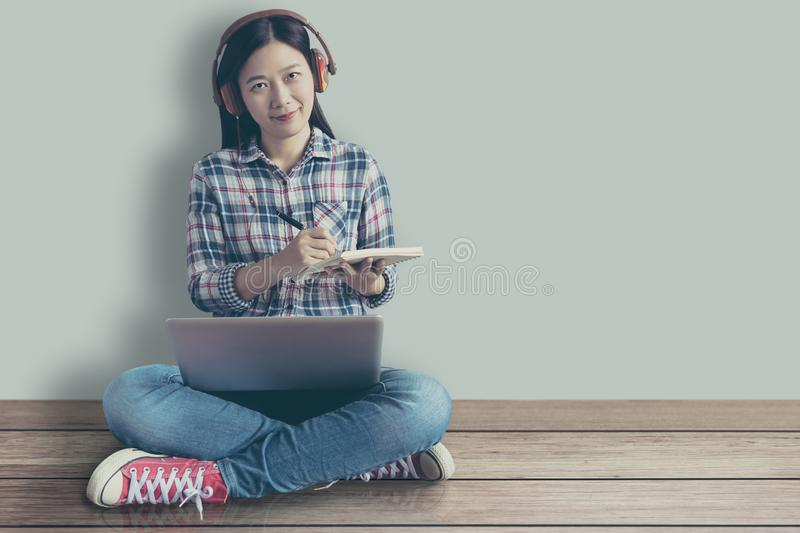 Female student relaxed sitting on a wooden floor at home and watching training online course and listening it with headphones stock image