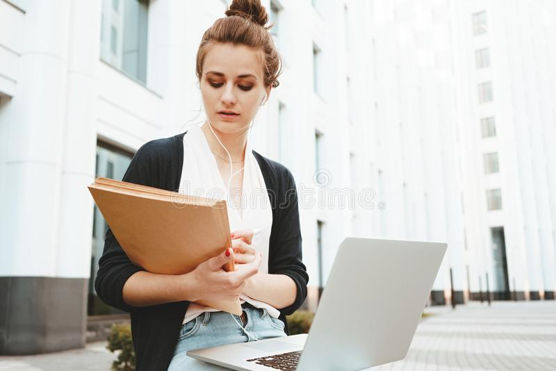 Female student sits in urban street near university and prepares for lecture with laptop. Thoughtful female student sits in urban street near university and royalty free stock images