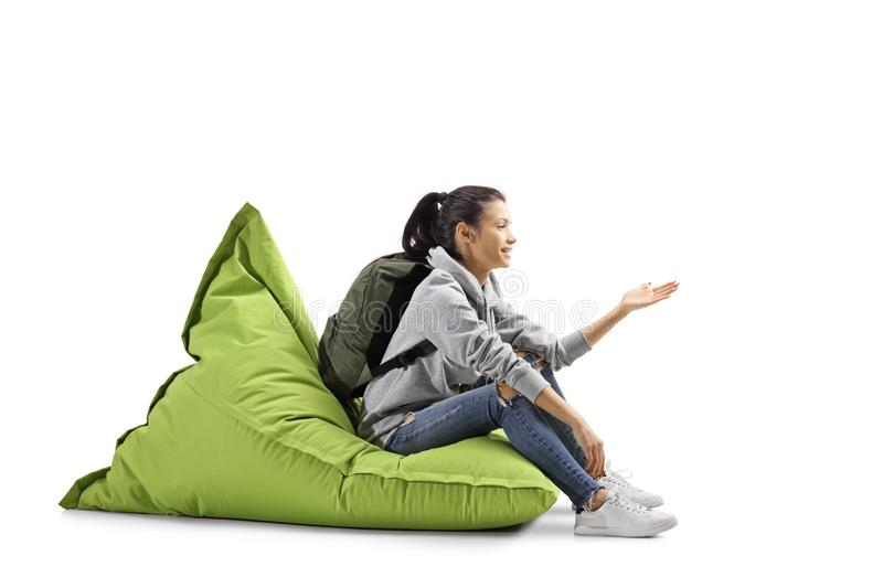 Female student sitting on a green bean bag and gesturing with hand. Isolated on white background royalty free stock photos