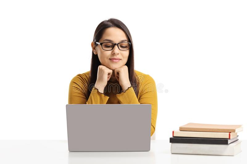 Female student sitting with a laptop and books stock image