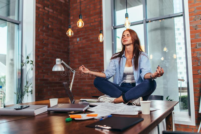 Female student sitting in lotus pose on table in her room meditating relaxing after studying and preparing for exam.  stock photography