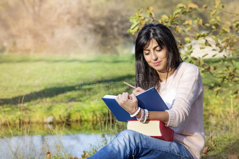Young Woman Studying with Books for Exams Outdoor. Female student sitting in a park with books stock images
