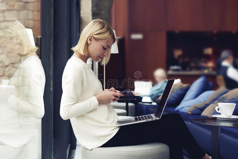 Female student sitting in university library while using technology. Modern business woman or young successful working on smartphone and laptop computer at