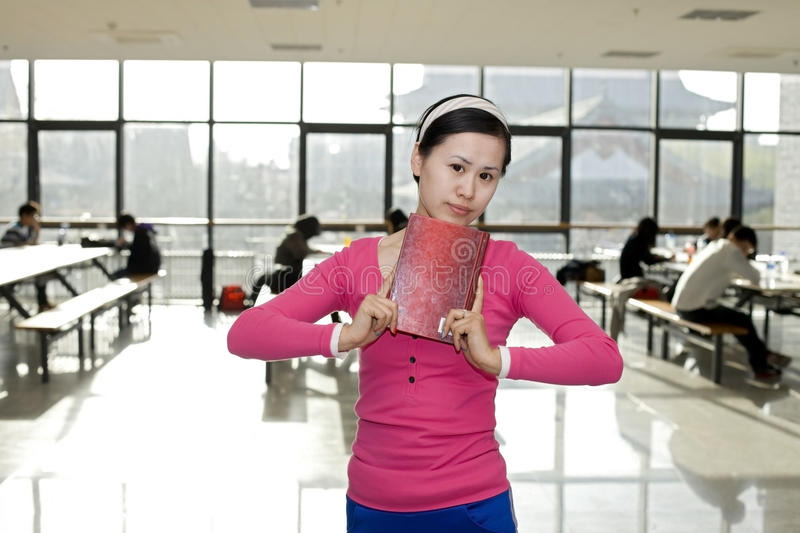 A female student standing with a book. A female student is standing in the teaching building with a book in hands royalty free stock images
