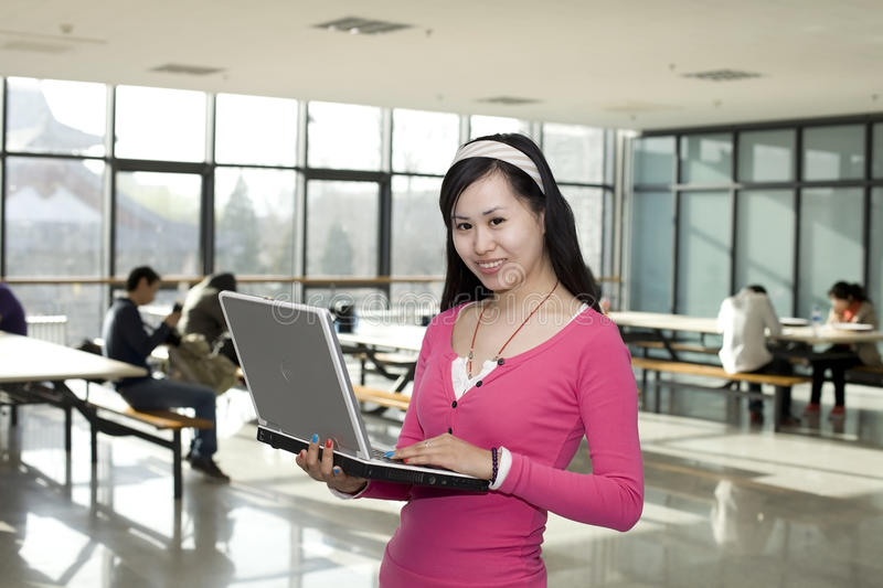 A female student standing with a computer. A happy female student standing in the teaching building with a computer in hands stock photo
