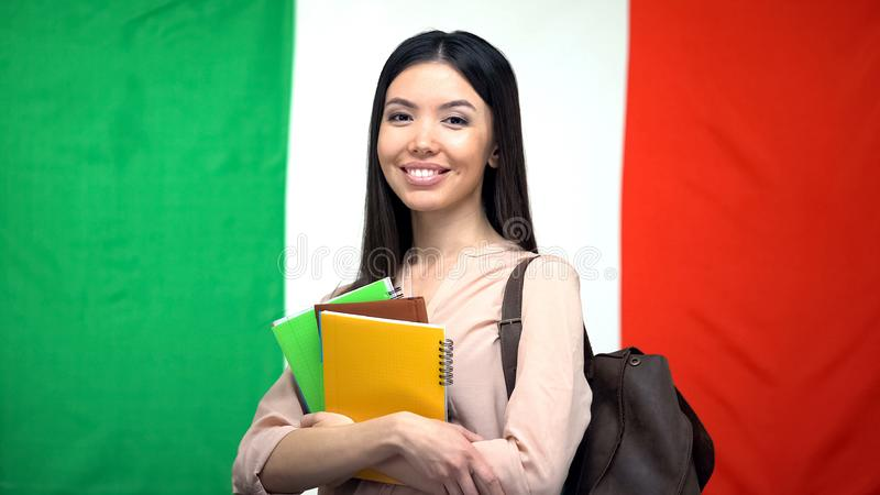 Female student standing with copybooks against Italian flag on background royalty free stock photography
