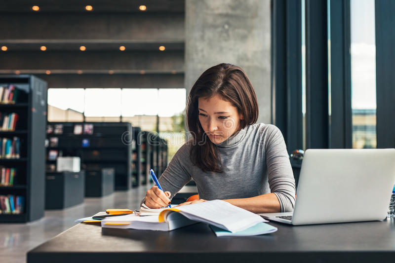 Female student studying at college library royalty free stock photo