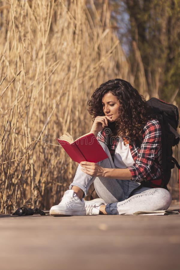 Female student studying outdoor. Female student sitting on the wooden lake docks, enjoying a suuny autumn day in nature and studying for an exam period stock photo