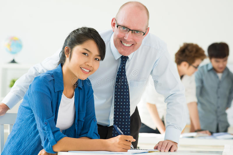 Female student. Teacher helping his student and looking at camera stock photography