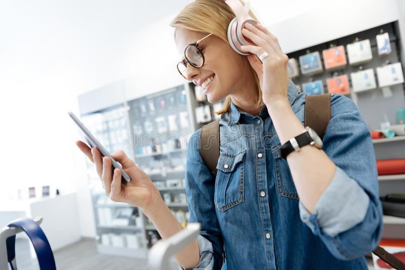 Female student trying out template headphones at electronics store. Which one to play. Cheerful female customer wearing glasses smiling widely and getting royalty free stock photography