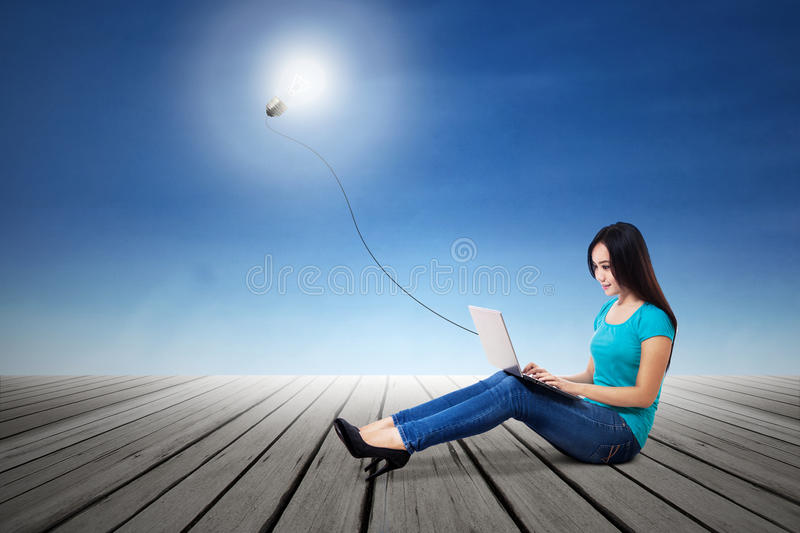 Female student typing on laptop with lit bulb stock photo