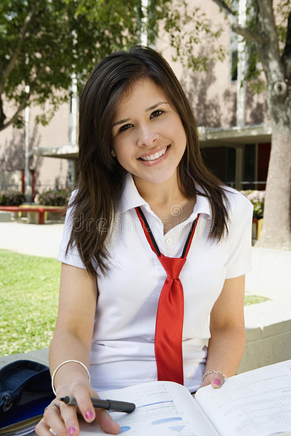 Female Student In Uniform Studying. Portrait of happy high school female student in uniform studying royalty free stock photos