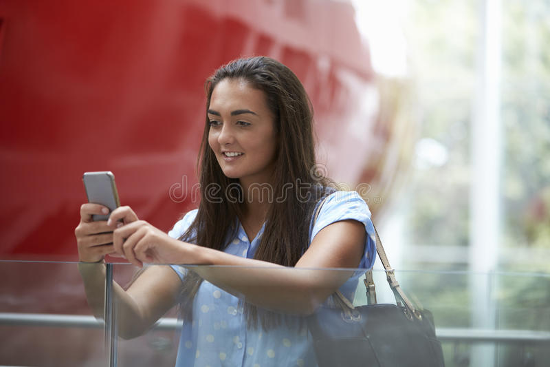 Female student uses smartphone in modern university building stock photos