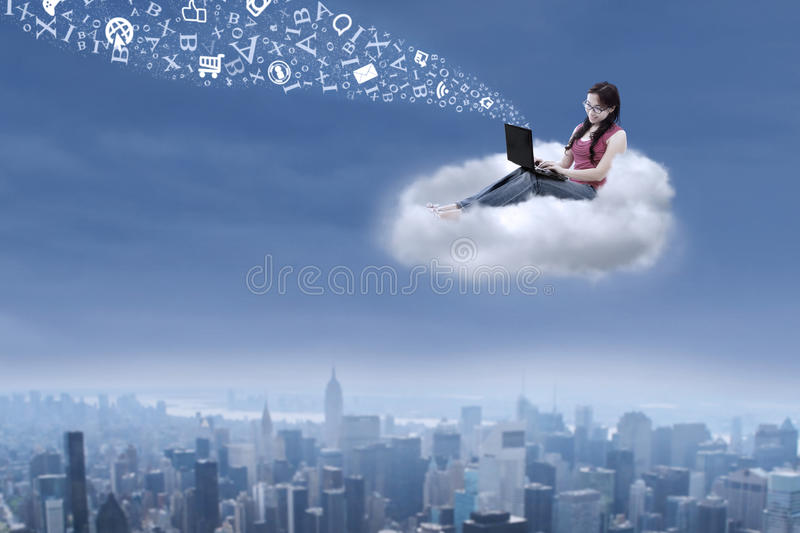 Female student using a laptop over cityscape royalty free stock photo