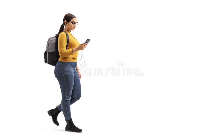 Female student walking and choosing a song from her mobile phone stock photography