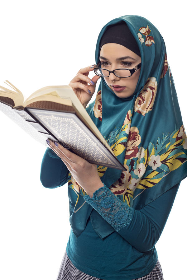 Female Student Wearing Hijab Reading a Book. Female foreign exchange student wearing glasses and a hijab reading a text book. The conservative outfit is stock images
