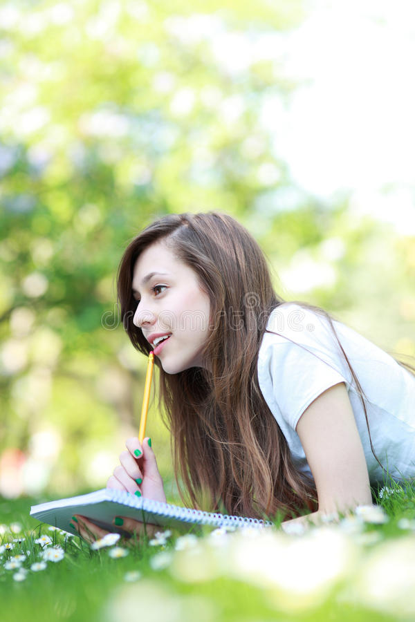 Female student with workbook outdoors. Shot of an attractive young woman outdoors royalty free stock photos