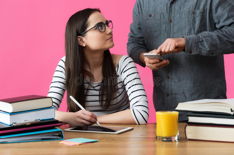 Female student working one to one with tutor. Tutor helping student to prepare for exams. stock photography