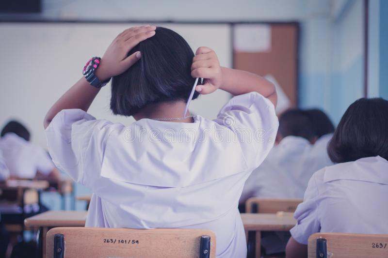 Female students is combing her hair in classroom. royalty free stock images