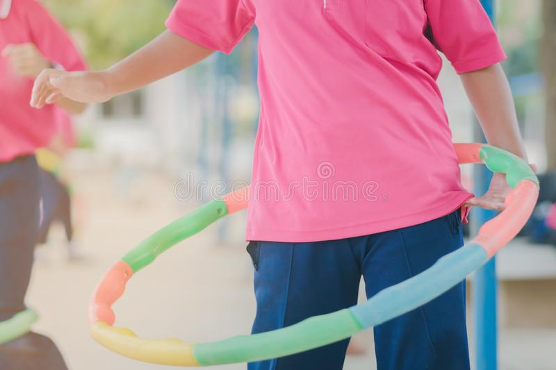 Female students doing exercise with a hula-hoop for a good healt. Hy at school royalty free stock photos