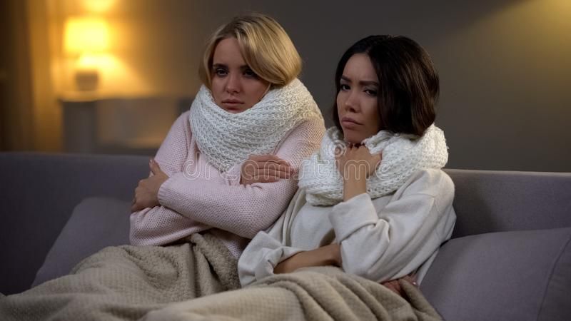 Female students with fever sitting on sofa in dormitory, flu virus, epidemic stock photography