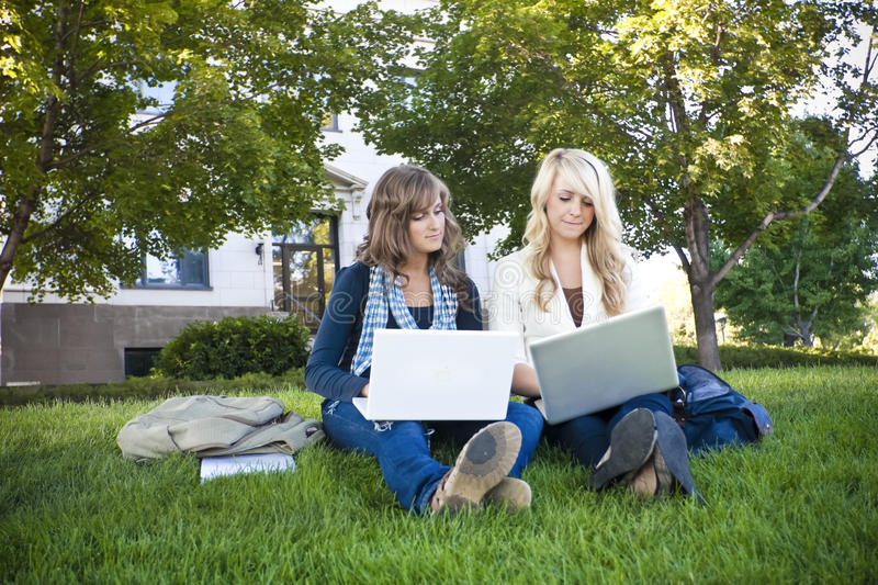 Female students studying on Laptop computers. Young, attractive female students outside an academic building study on their laptop computers royalty free stock images