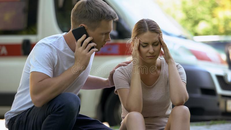 Female suffering headache, not indifferent man calling ambulance, first aid. Female suffering headache, not indifferent men calling ambulance, first aid, stock royalty free stock photo