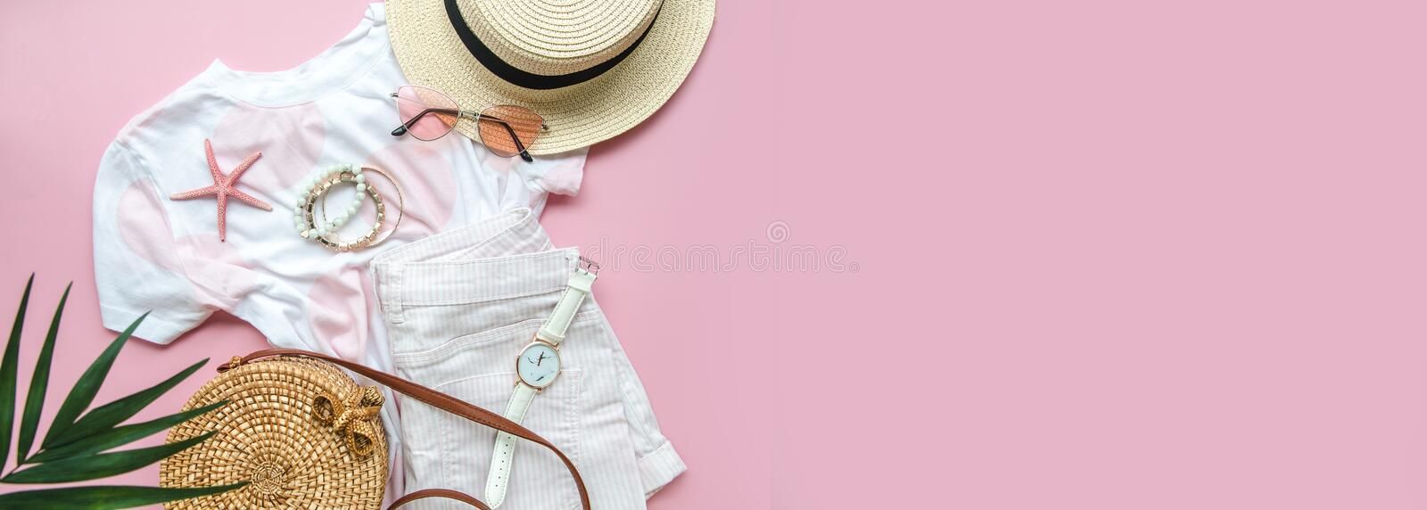 Female summer beach clothes and accessories on a pink background. Top view wide banner with copy space for travel agency.  stock photo